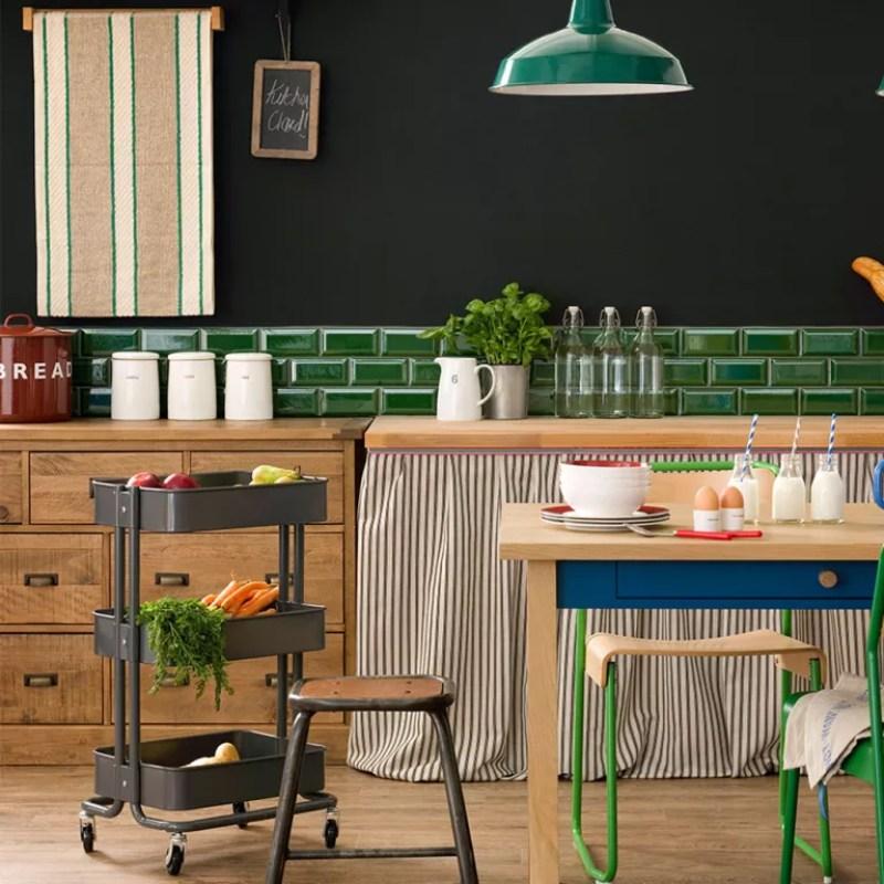 Black kitchen with green splashback tiles wooden cabinets an d portable black storage trolley