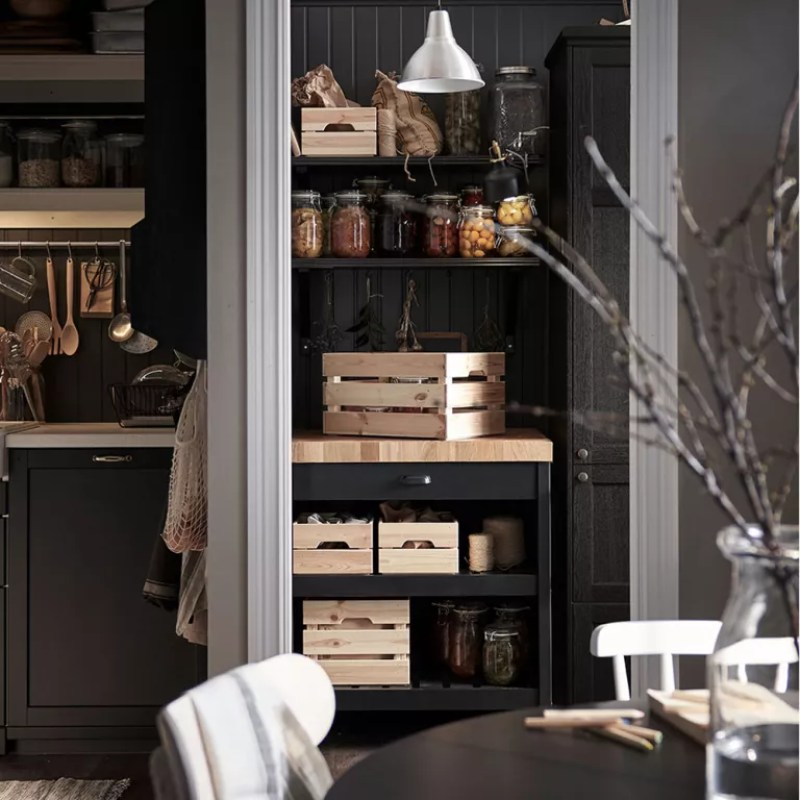 Black kitchen with portable kitchen island inside pantry cupboard