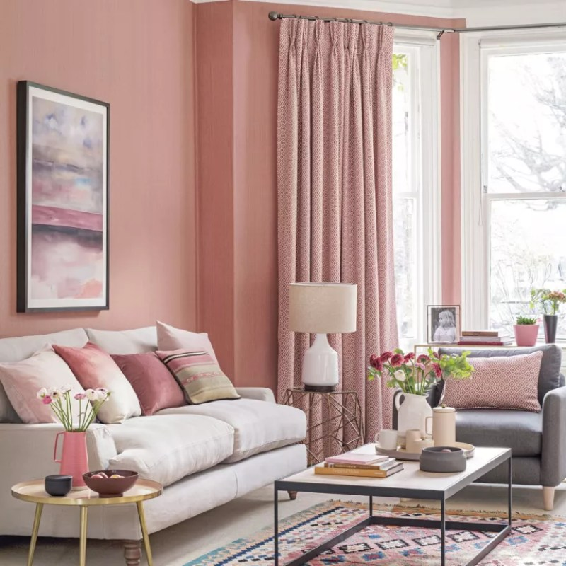 Peachy pink living room walls, cream sofa and pink curtains