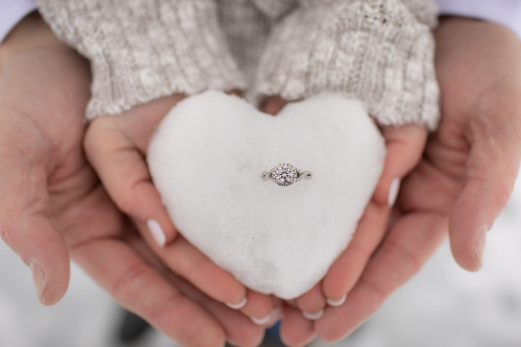 hands holding engagement ring  in heart shaped snowball