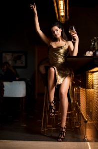 Glamour picture of Beautiful model in Gold at the bar with white wine