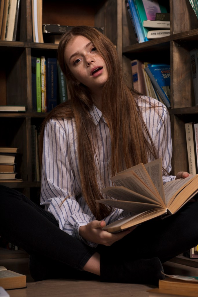 Beautiful long red hair girl in a library natural look