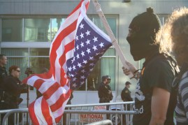 A protester holds an American flag upside in front of police officers during a protest while President Obama was visiting Oakland as part of his campaign fundraising tour for his second term in office July 23, 2012. Photo by Kevin Skahan.