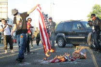 A protester burns an American flag during a rally against President Obama in Oakland July 23, 2012. Photo by Kevin Skahan.