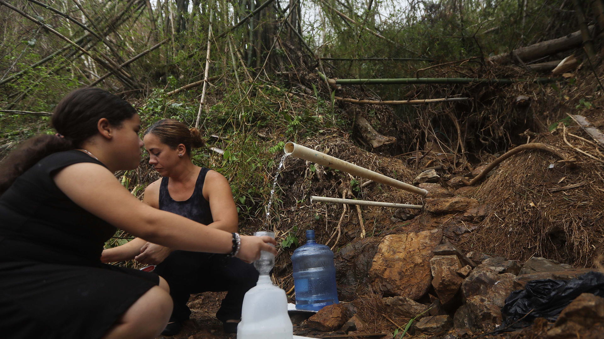 People whose homes no longer have running water fill jugs with spring water over two weeks after Hurricane Maria hit the island, on Oct. 7, 2017, in Naranjito, Puerto Rico. (Credit: Mario Tama/Getty Images)