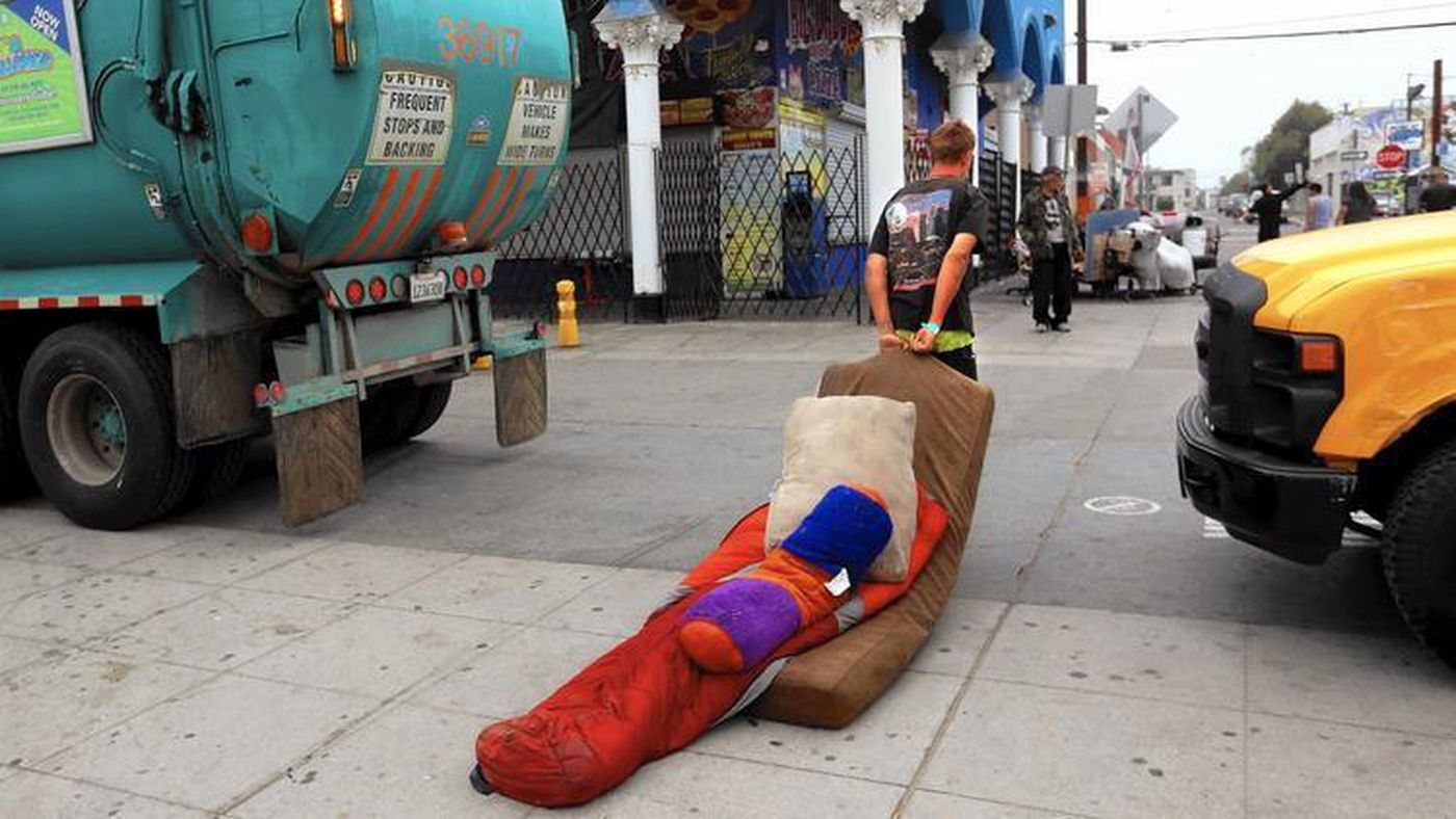 Marcus Steinlechner drags his bedding between a garbage truck and a city sanitation truck during a sweep of homeless encampments on the boardwalk at Venice Beach on June 26, 2015. (Credit: Los Angeles Times)