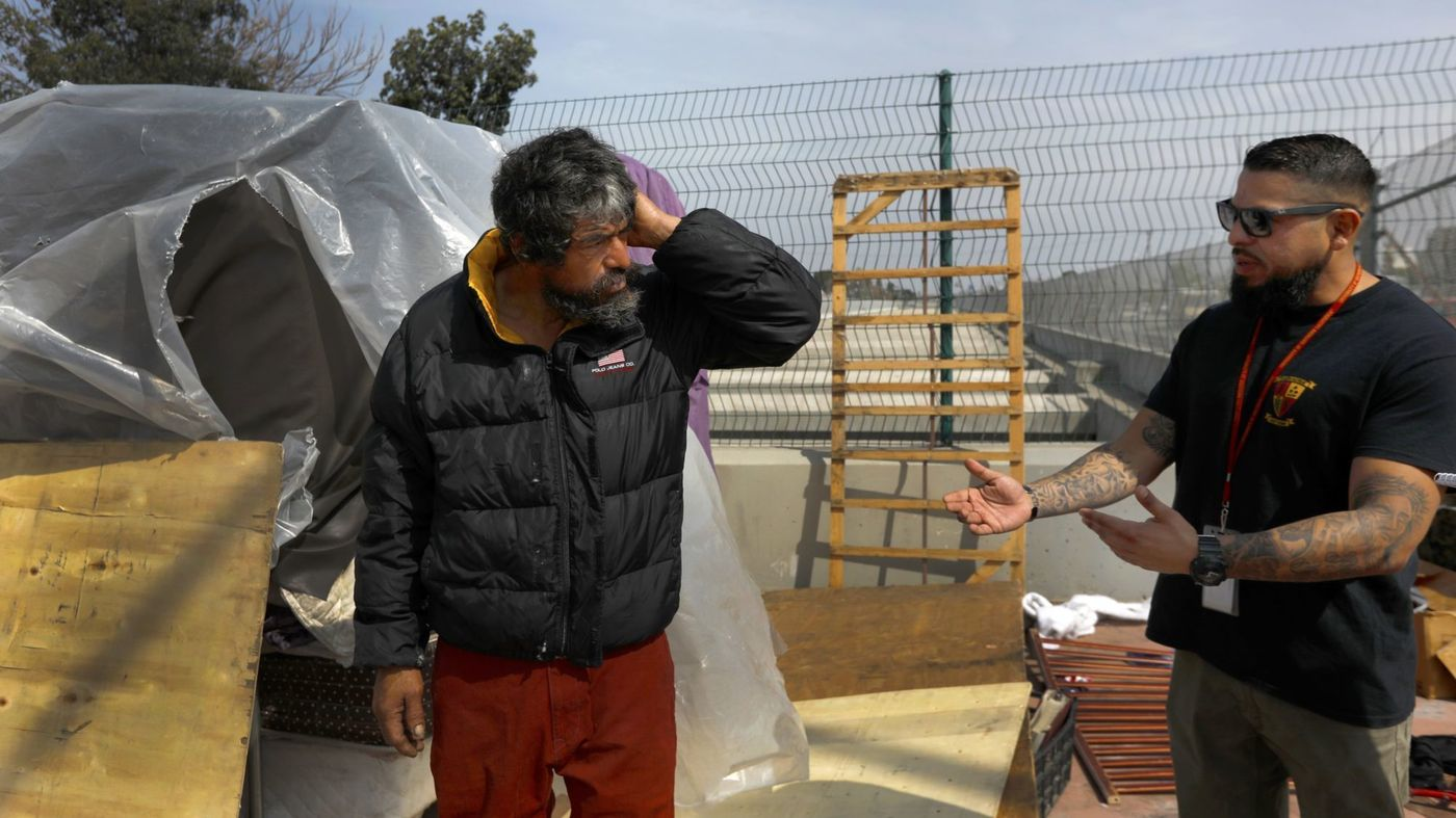 Adrian Tafoya, right, with the Homeless Outreach Program Integrated Care System talks to Jesus (no last name given) in Compton in an undated photo. (Credit: Francine Orr / Los Angeles Times)