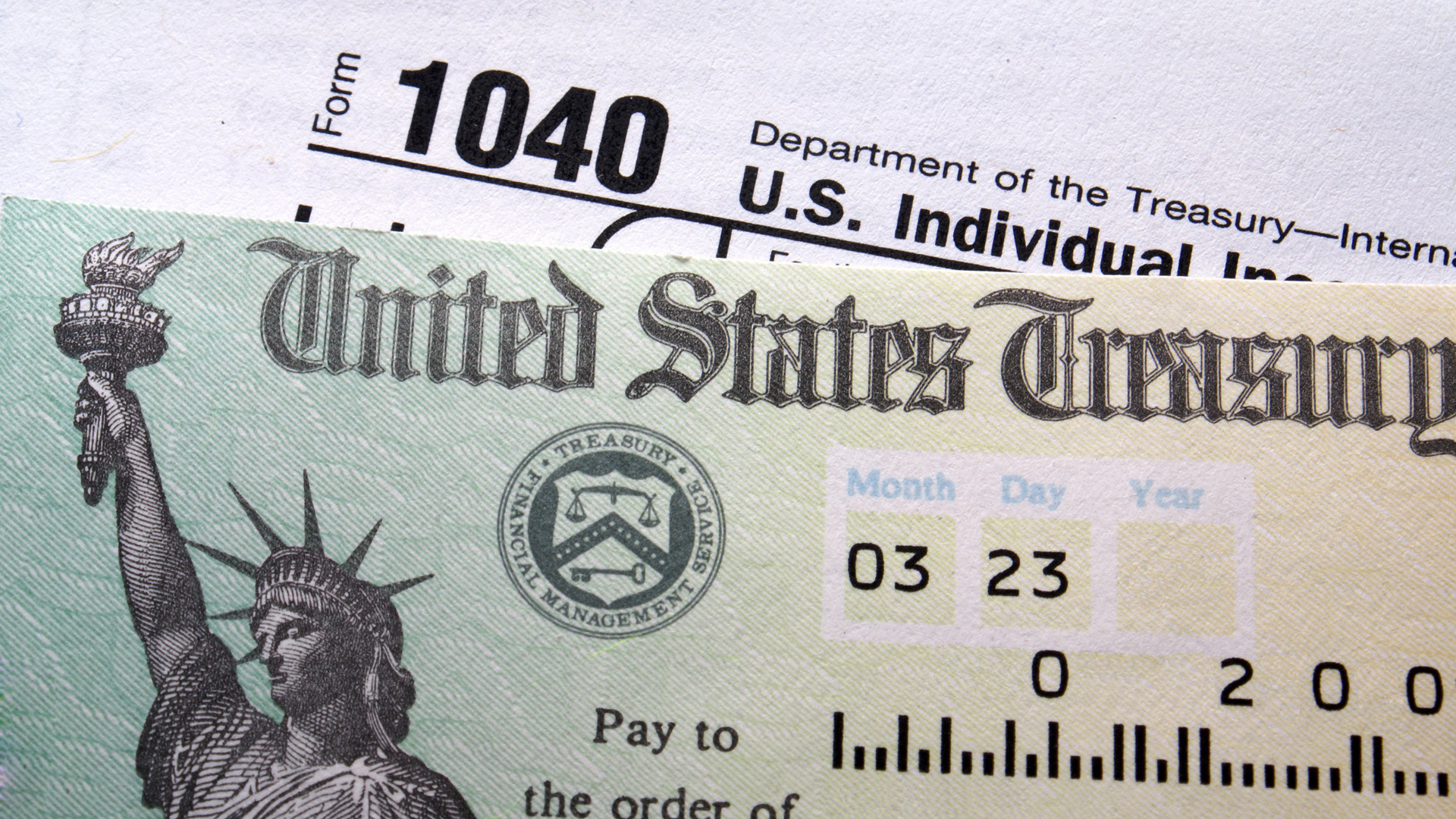 A tax form and a check from the U.S. Treasury are seen in a file image. (Credit: Shutterstock)