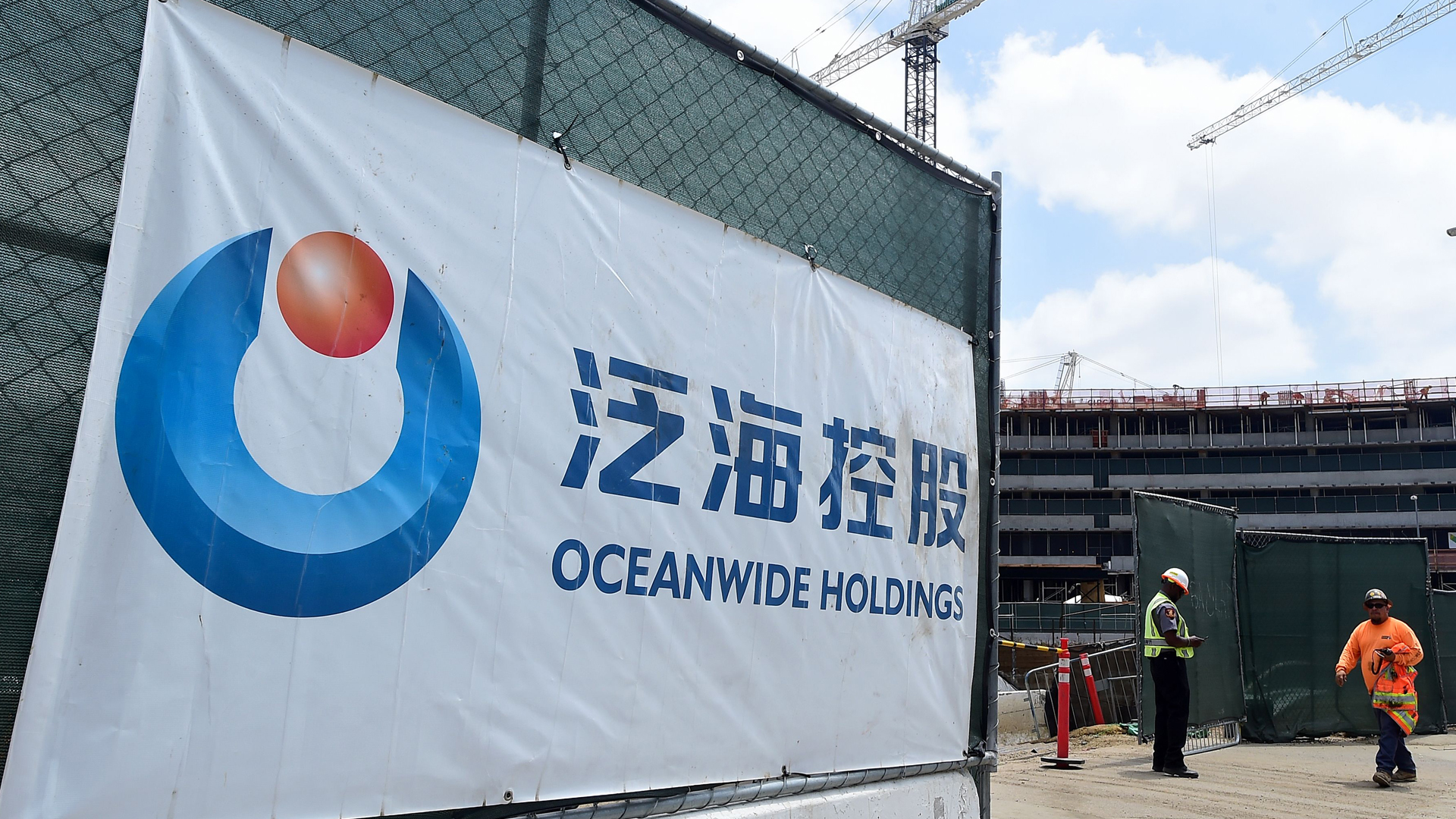 A banner of China's Oceanwide Real Estate Group is displayed at the construction site of the property, purchased in 2014, located across the street from the Staples Center in Los Angeles, on May 17, 2016. A huge surge in Chinese buying of both commercial U.S. real estate and residential property last year took their five-year investment total to more than $110 billion, according to a study from the Asia Society and Rosen Consulting Group, as Chinese nationals became the largest foreign buyers of U.S. homes. (Credit: FREDERIC J. BROWN/AFP/Getty Images)