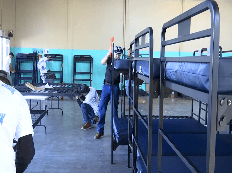 Volunteers work to put together beds funded by donations from weed dispensaries at a temporary homeless shelter in Oxnard on Feb. 25, 2019. (Credit: KEYT)