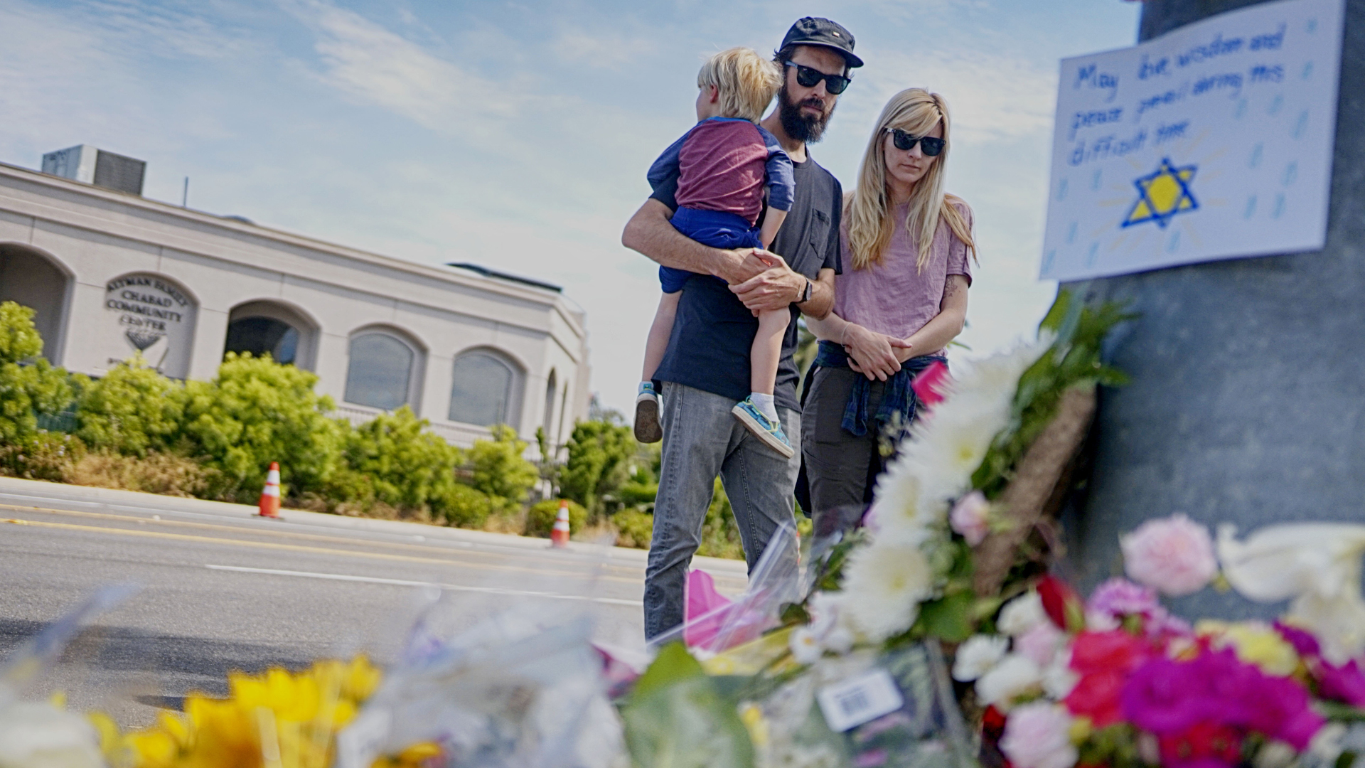 Mourners look over a make-shift memorial across the street from the Chabad of Poway Synagogue on April 28, 2019, in Poway, California.(Credit: Sandy Huffaker/AFP/Getty Images)