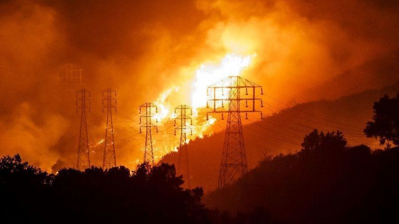 Flames from the Thomas fire whip around utility power lines in Sycamore Canyon on Dec. 16, 2017. (Credit: Marcus Yam / Los Angeles Times)