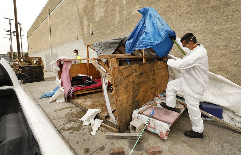 Two of those assisting cleanups at L.A. homeless encampments, Jesus Sanchez, left, and Javier Villarreal, make their way through one effort. (Credit: Al Seib / Los Angeles Times)