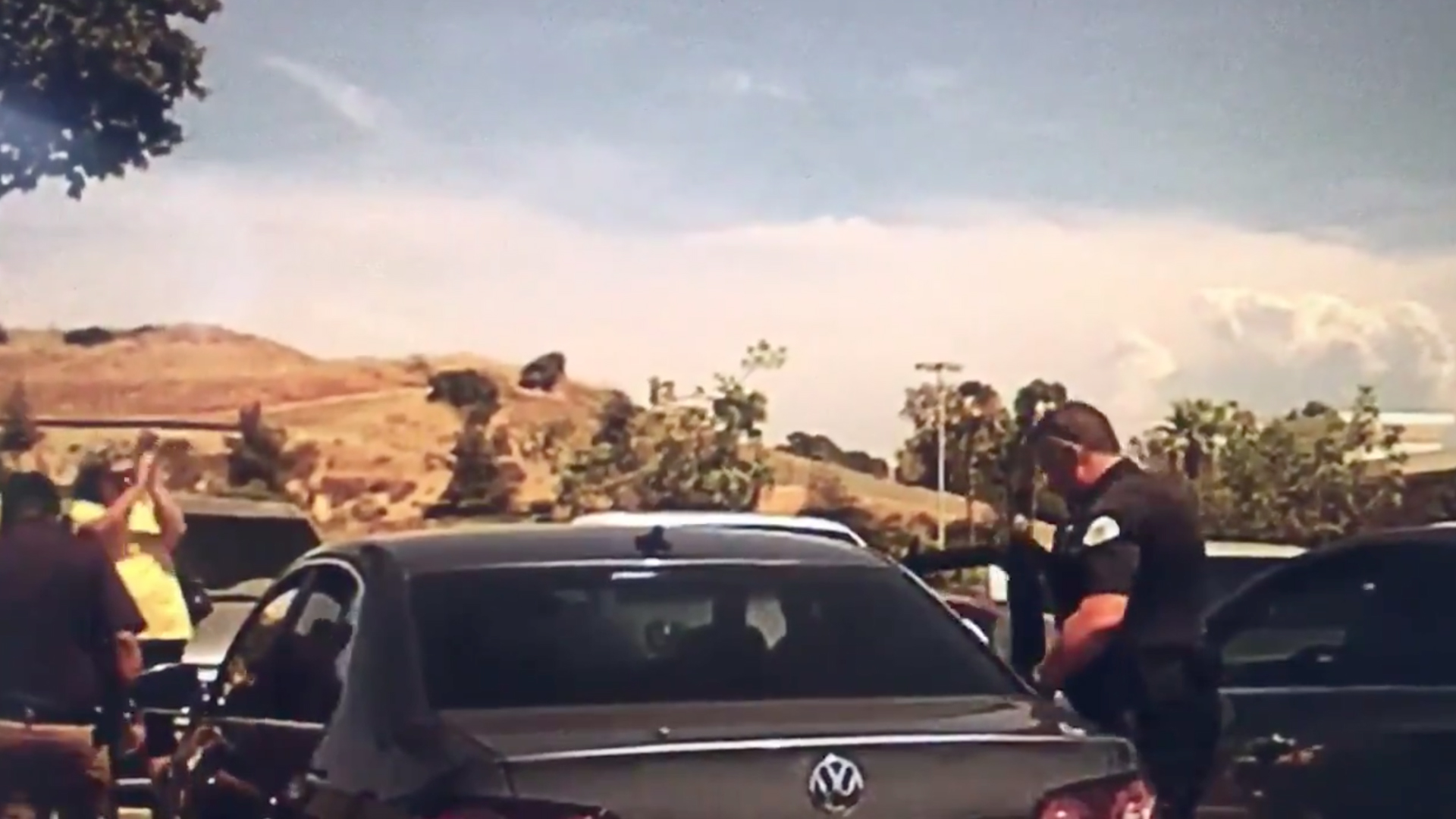 A bystander claps as police remove a Dachshund from a car in a West Covina parking lot as temperatures neared 100 degrees on July 25, 2019. (Credit: West Covina Police Department)
