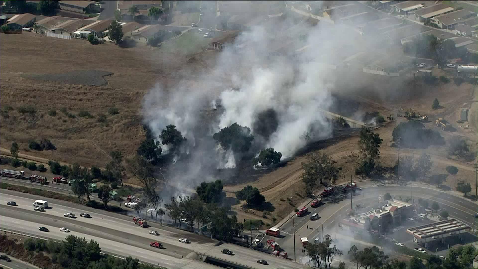 Firefighters battle a brush fire along the 210 Freeway in Sylmar on Aug. 9, 2019. (Credit: KTLA)