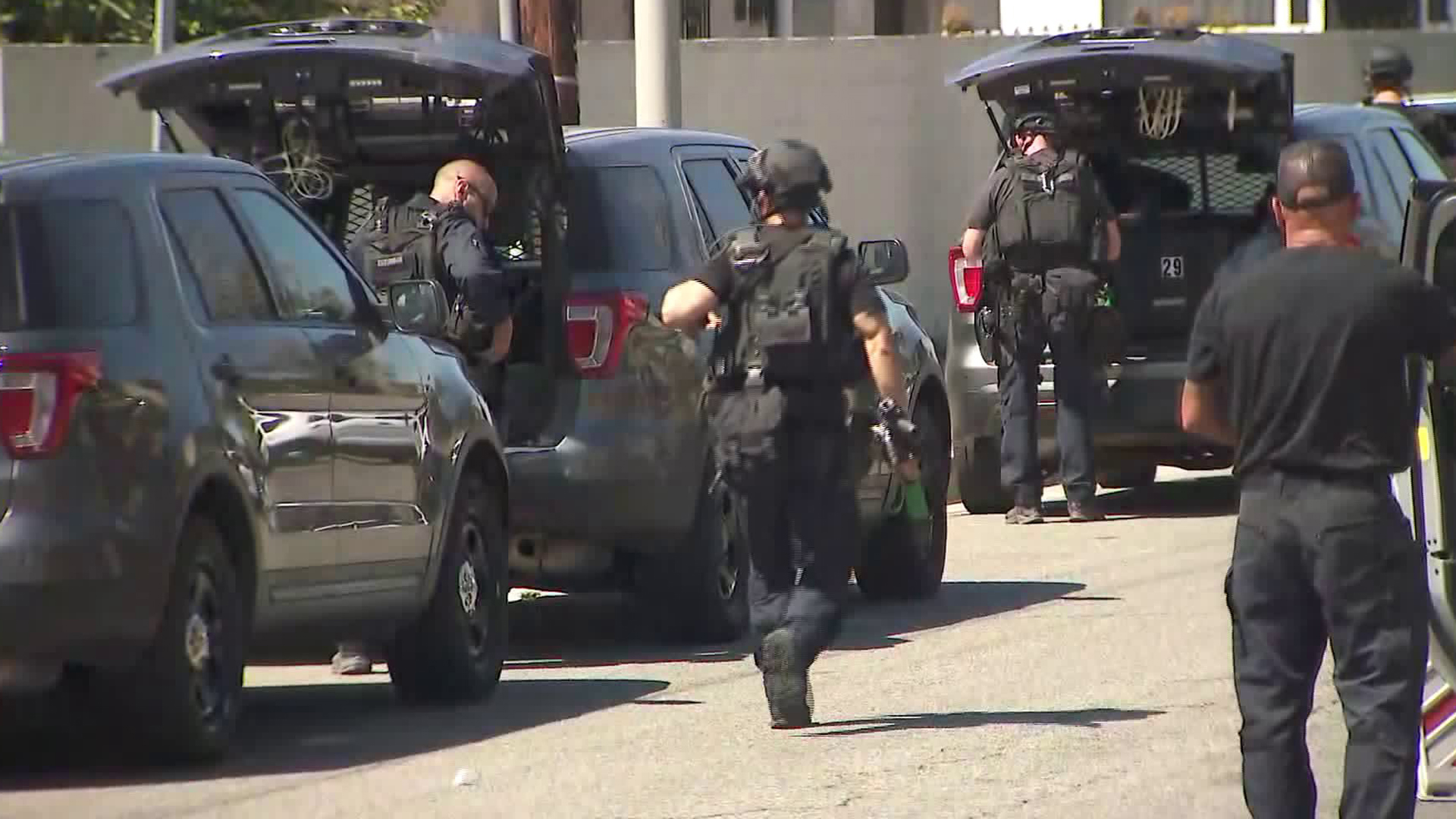 Uniformed officers walk through the scene in the South Los Angeles neighborhood of Vermont Knolls, where a person was fatally shot, on Aug. 29, 2019. (Credit: KTLA)