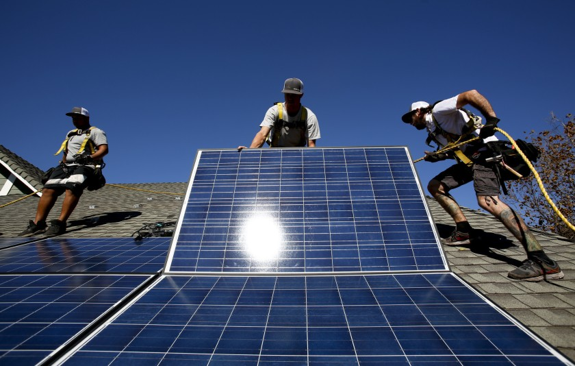A crew installs rooftop solar panels at a home in Camarillo in 2013. (Credit: Anne Cusack / Los Angeles Times)