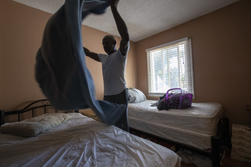 Sam Blake makes a bed after doing laundry at the Blake Home in Sylmar. Funding problems have led many such homes to close, forcing some tenants who are poor and unable to care for themselves into homelessness. (Credit: Brian van der Brug/Los Angeles Times)