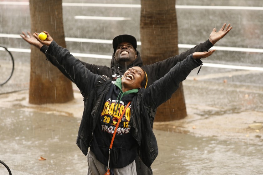 Tramell Waller and Keena Spencer welcome the rain and hail falling in downtown Los Angeles on Nov. 20, 2019. (Credit: Al Seib / Los Angeles Times)