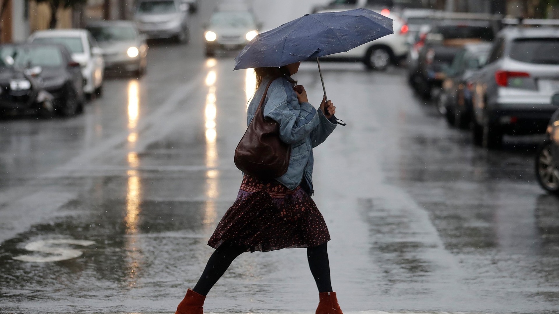 A woman walking in the rain in San Francisco. (Credit: Jeff Chiu/AP)