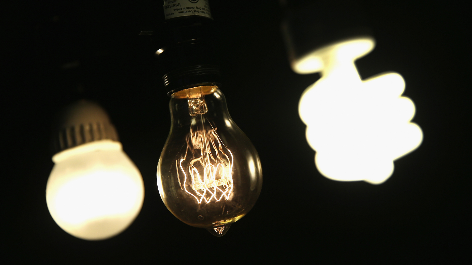A vintage-style incandescent light bulb, center, is shown with an LED light bulb, left, and a compact florescent bulb in Chicago, Illinois, on Dec. 27, 2013. (Credit: Scott Olson / Getty Images)