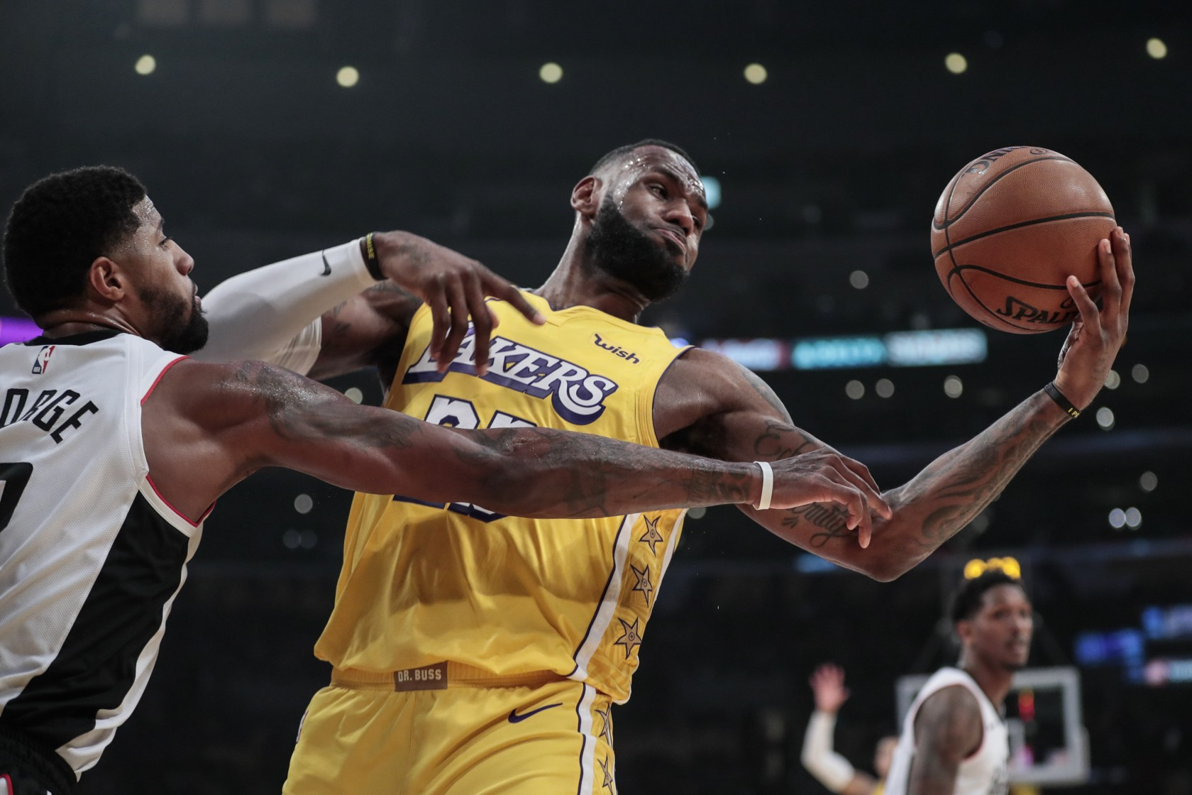 Lakers forward LeBron James tries to control a rebound against Clippers forward Paul George. (Credit: Robert Gauthier/ Los Angeles Times)