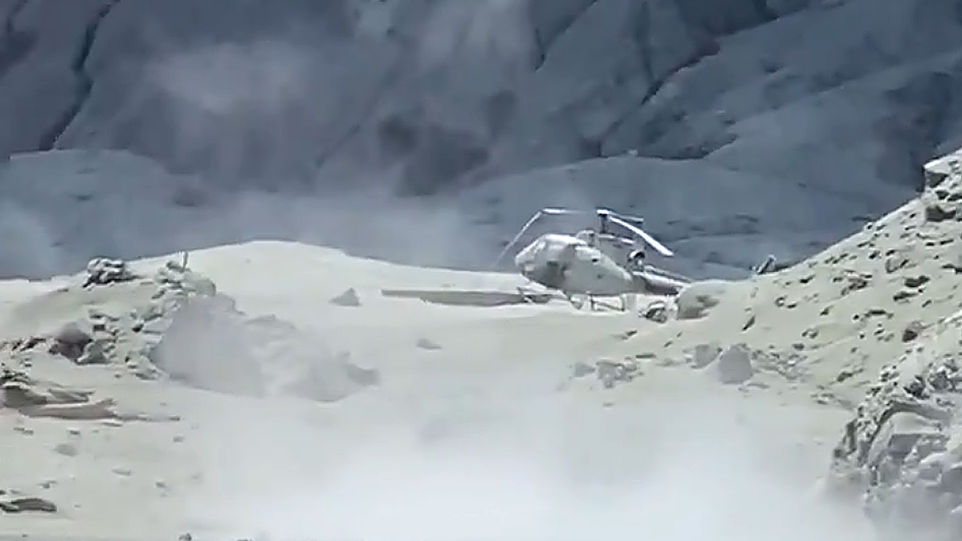 An image of a damaged helicopter on White Island after the eruption. (Credit: Twitter/Michael Schade via CNN)