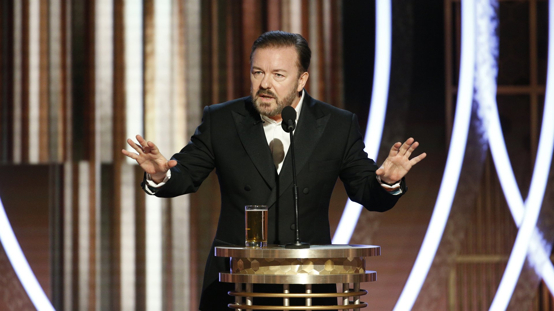 In this handout photo provided by NBCUniversal Media, LLC, host Ricky Gervais speaks onstage during the 76th Annual Golden Globe Awards at The Beverly Hilton Hotel on January 5, 2020 in Beverly Hills, California. (Credit: Paul Drinkwater/NBCUniversal Media, LLC via Getty Images)