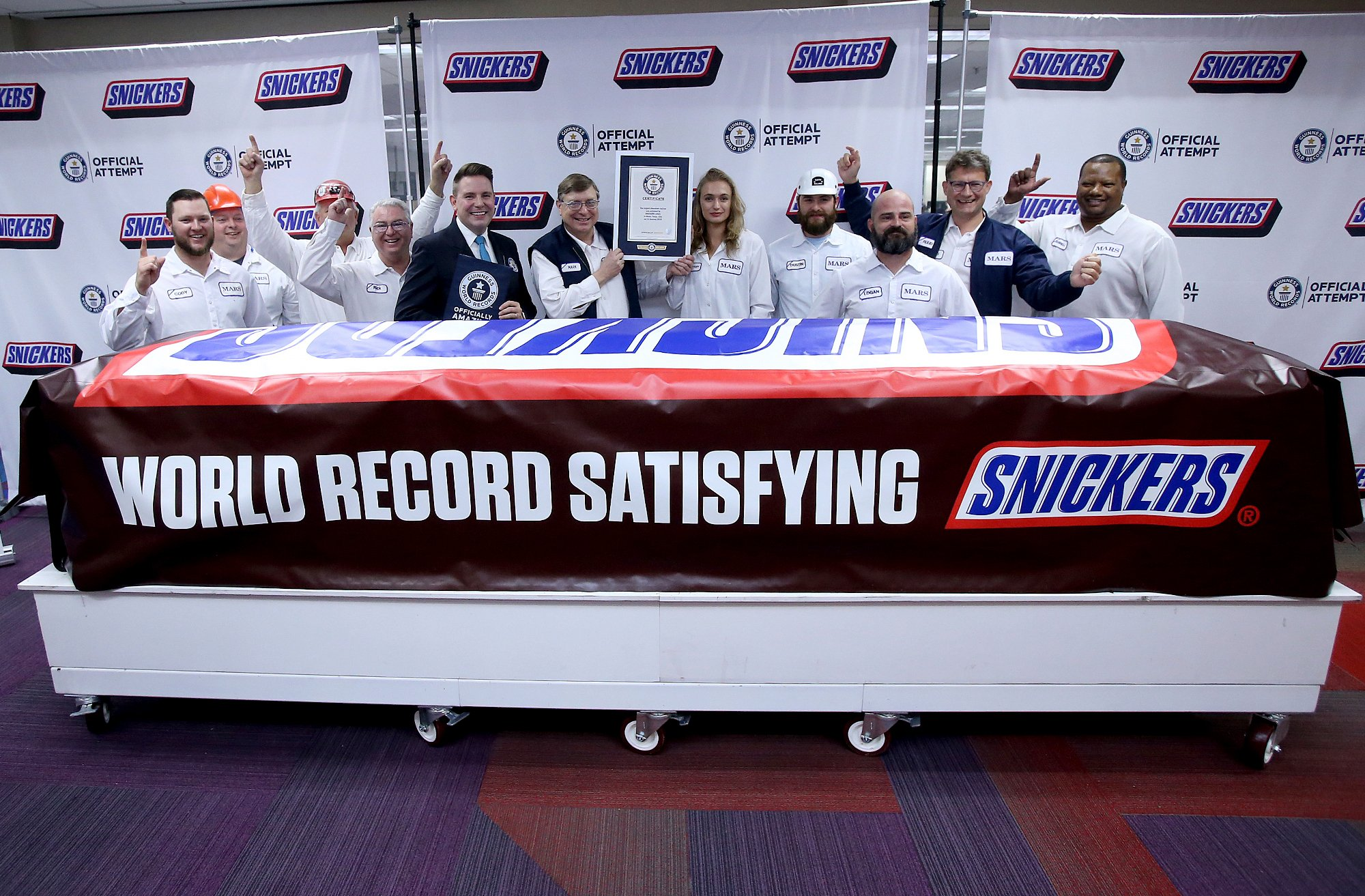 Mars Wrigley employees pose with a giant Snickers bar made at the plant in Waco, Texas. (Credit: Jerry Larson/AP via CNN Wire)