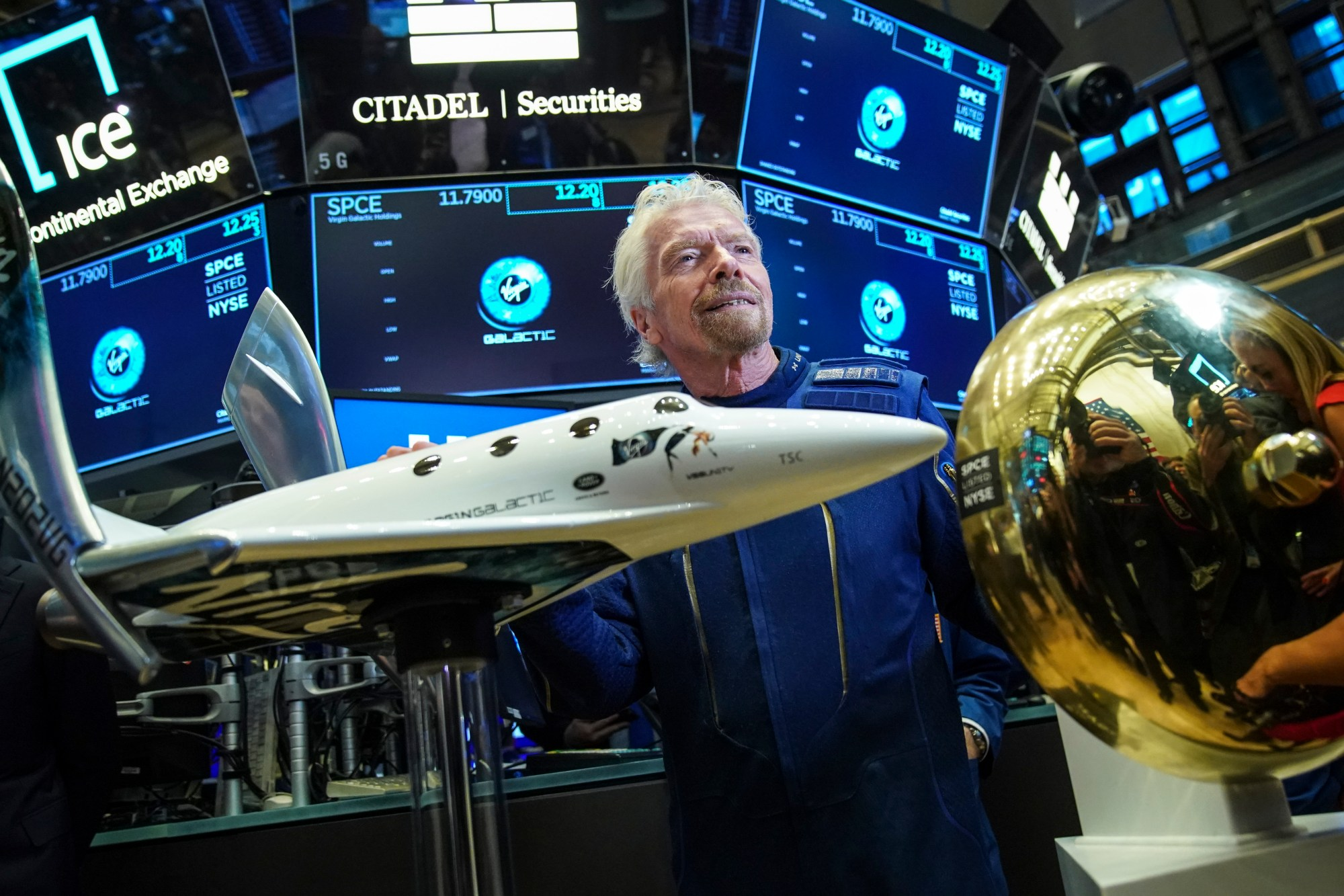 Sir Richard Branson, founder of Virgin Galactic, poses for photographs before ringing a ceremonial bell on the floor of the New York Stock Exchange on the company's first day of trading shares, Oct. 28, 2019. (Credit: Drew Angerer / Getty Images)