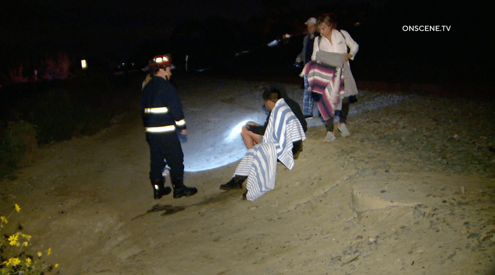 Firefighters speak with people rescued after apparently being dumped from a panga boat off Del Mar on Feb. 28, 2020.(Credit: Onscene.TV)