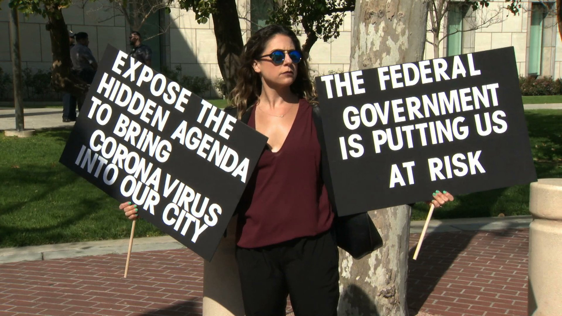A woman demonstrates against a proposal to quarantine coronavirus patients at a Costa Mesa facility on Feb. 24, 2020. (Credit: KTLA(