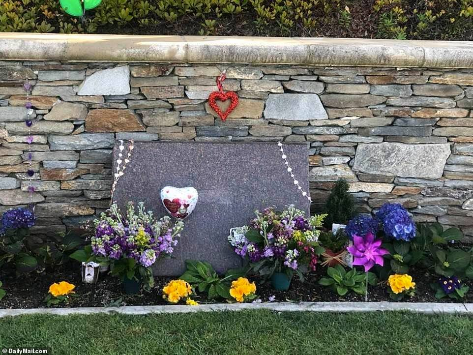 An unmarked headstone surrounded by purple and yellow flowers is seen at Pacific View Memorial Park and Mortuary. (Credit: Daily Mail)