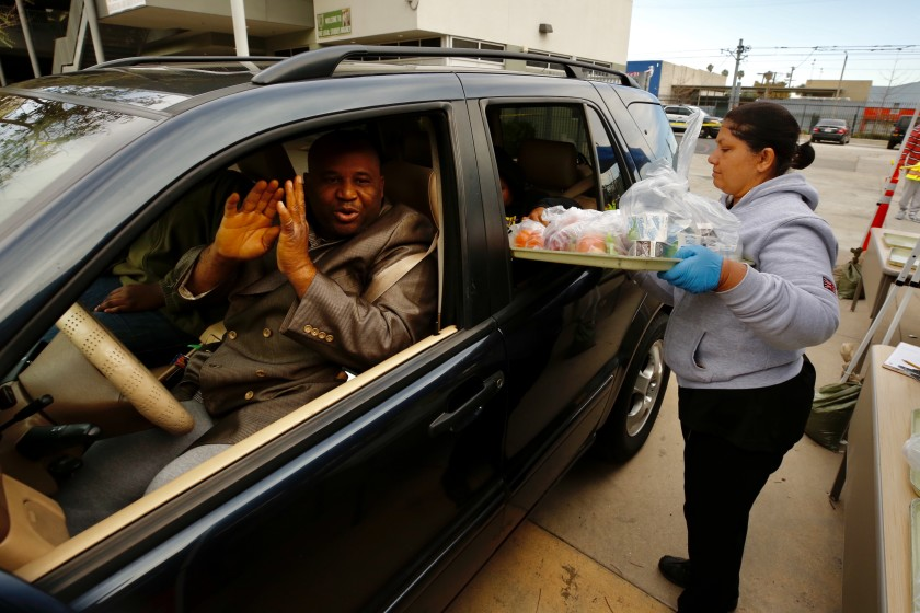 LAUSD employee Benjula Prasad serving meals-to-go on March 18, 2020, at Dorsey High. (Al Seib/Los Angeles Times)