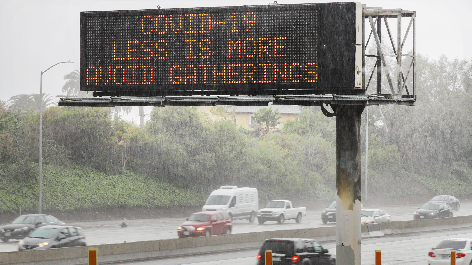An electronic sign reads 'COVID-19 Less Is More Avoid Gatherings' along the I-10 Freeway on March 14, 2020, in Los Angeles. (Mario Tama/Getty Images)