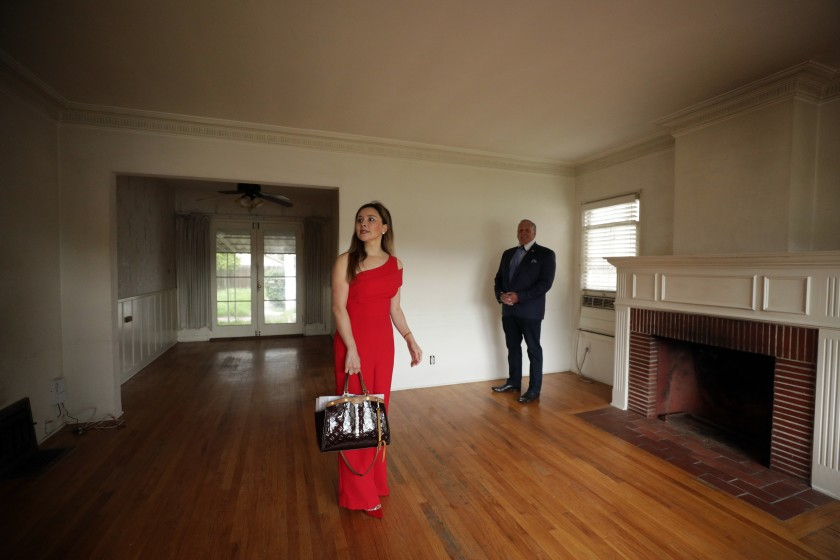 Real estate investor Celine Yan and her agent, Jeff Brager, look over a North Hollywood house she is purchasing. (Myung J. Chun / Los Angeles Times)