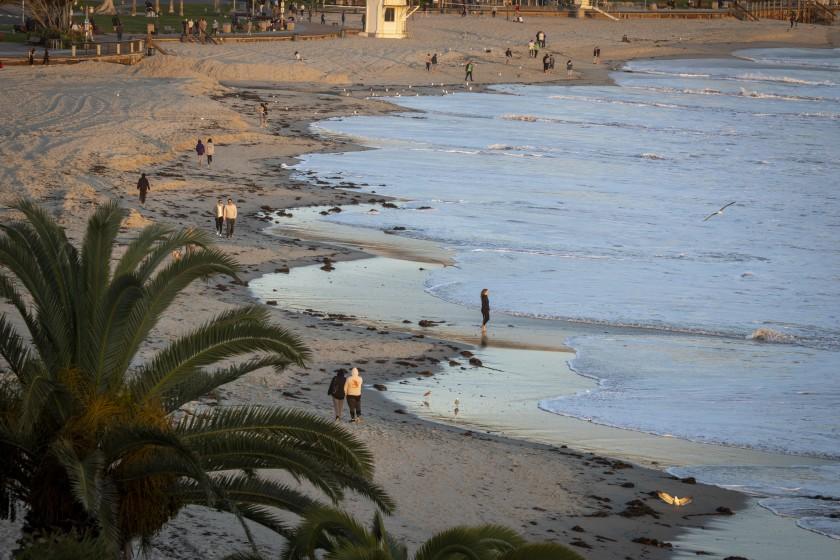 People walk along the beach near Main Beach in Laguna Beach on March 18, 2020. (Allen J. Schaben / Los Angeles Times )