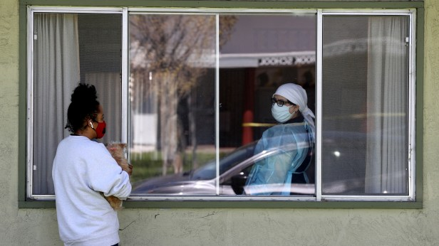 A woman talks with a nurse through a window as she visits her father who is a patient at a nursing home with a cluster of COVID-19 cases in Hayward, California, on April 14, 2020. (Justin Sullivan/Getty Images)