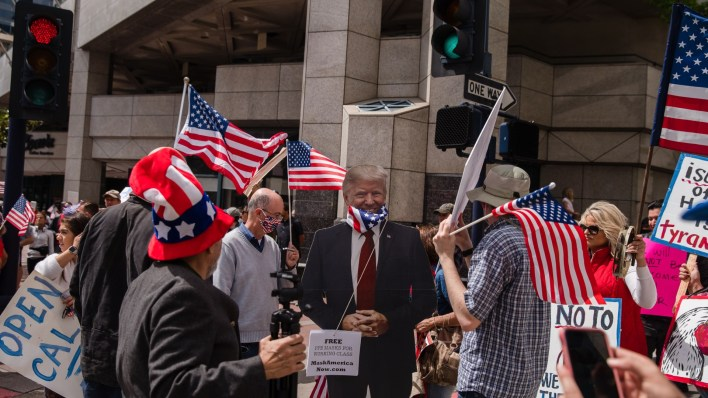 A Trump cutout with a US flag around its neck is seen next to protesters rallying in downtown San Diego against California's stay at home order to prevent the spread of the novel coronavirus, which causes COVID-19, on April 18, 2020. (Ariana Drehsler/AFP/Getty Images)