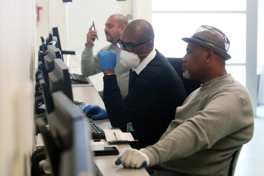 Stanley Smith, center, with South L.A. WorkSource Center helps Gregory Allen, right, with a job search.(Dania Maxwell/Los Angeles Times)