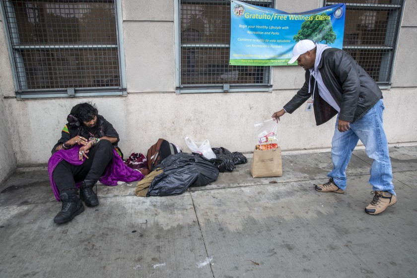 Outreach nurse Kenya Smith, right, leaves food for Davis Soto, who is homeless, in March 2020 in Los Angeles. (Brian van der Brug / Los Angeles Times)