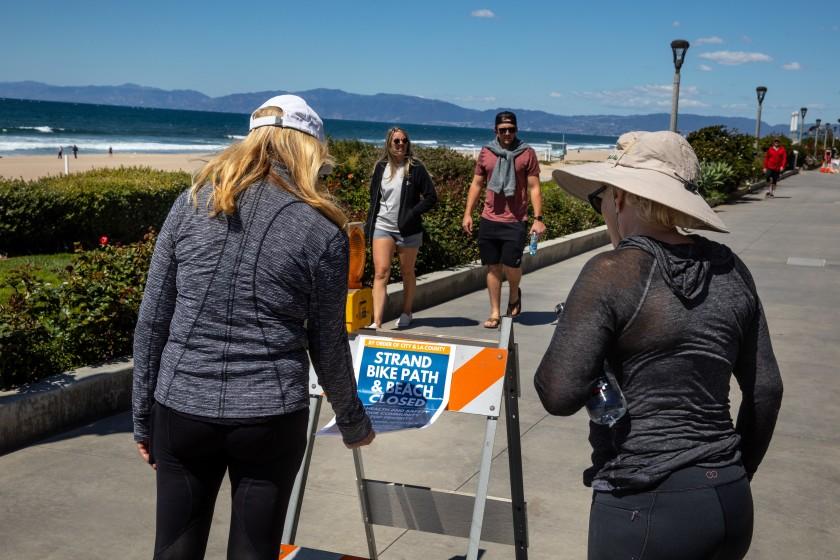 People stop to read a sign on the Strand in Manhattan Beach in March 2020 after officials closed all Los Angeles County beaches. (Jay L. Clendenin / Los Angeles Times)