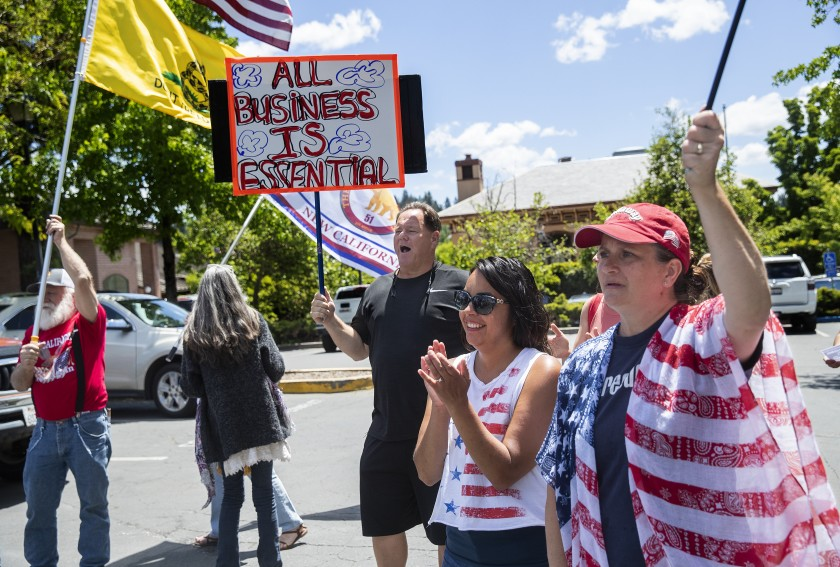 Placer County resident Jerry O'Brien holds a sign as he joins other demonstrators in a rally protesting California's stay-at-home order on May 22, 2020. (Mel Melcon / Los Angeles Times)