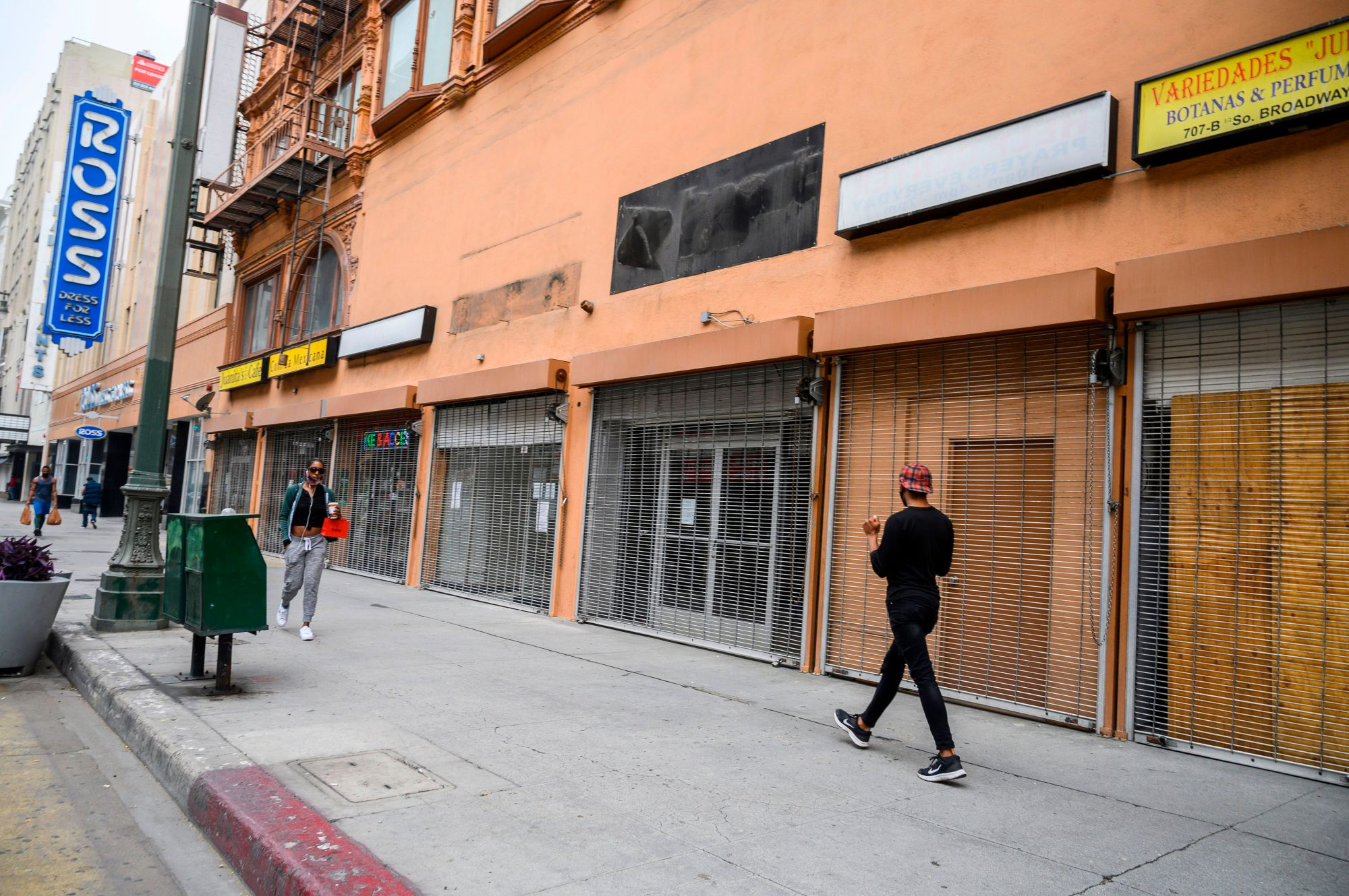 People walk past closed shops in downtown Los Angeles on April 30, 2020. (ROBYN BECK/AFP via Getty Images)