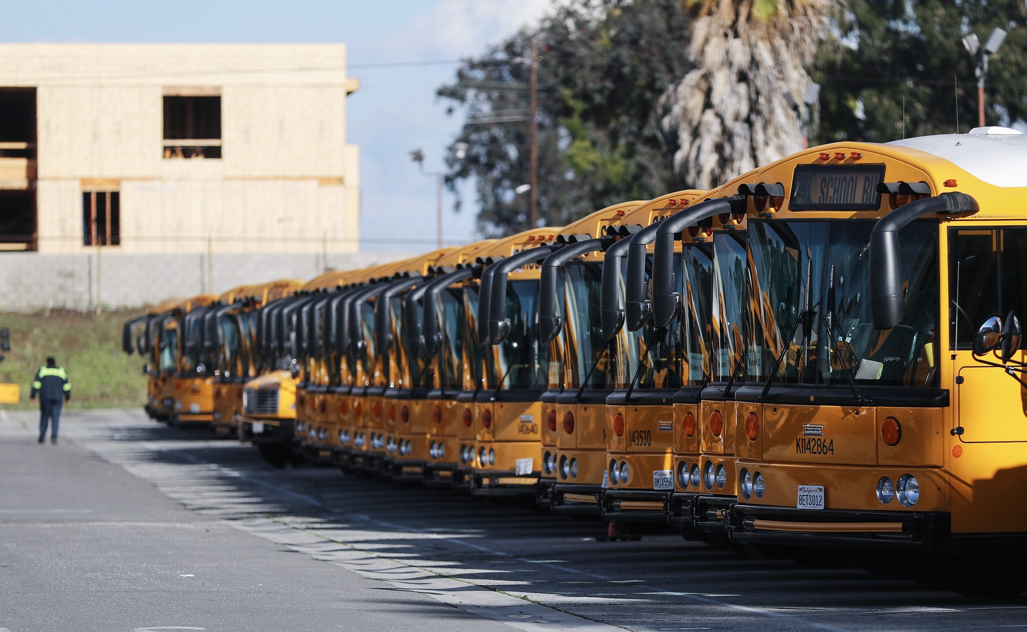 School buses are seen parked in a lot while schools schools stay closed in response to the coronavirus outbreak, on March 17, 2020, in Gardena. (Mario Tama/Getty Images)