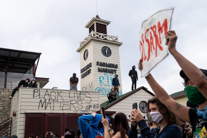 "Protesters shout, ""Hands up, don't shoot,"" outside The Grove in the Fairfax District on May 30, 2020, after demonstrators outraged over the death of George Floyd in Minneapolis converged on the area. (Kent Nishimura / Los Angeles Times)"