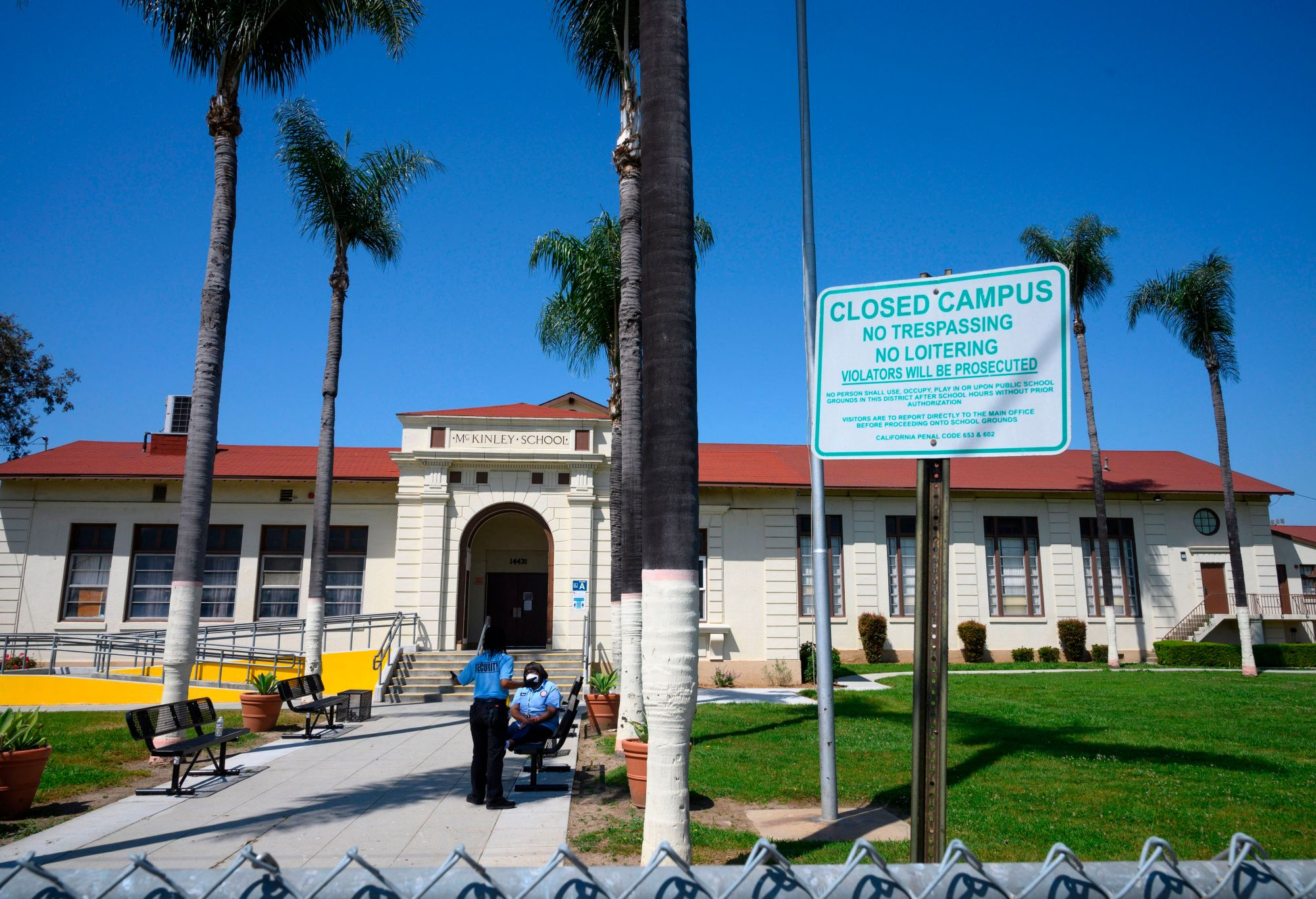 Two security guards talk on the campus of the closed McKinley School, part of the Los Angeles Unified School District system, in Compton on April 28, 2020. (ROBYN BECK/AFP via Getty Images)