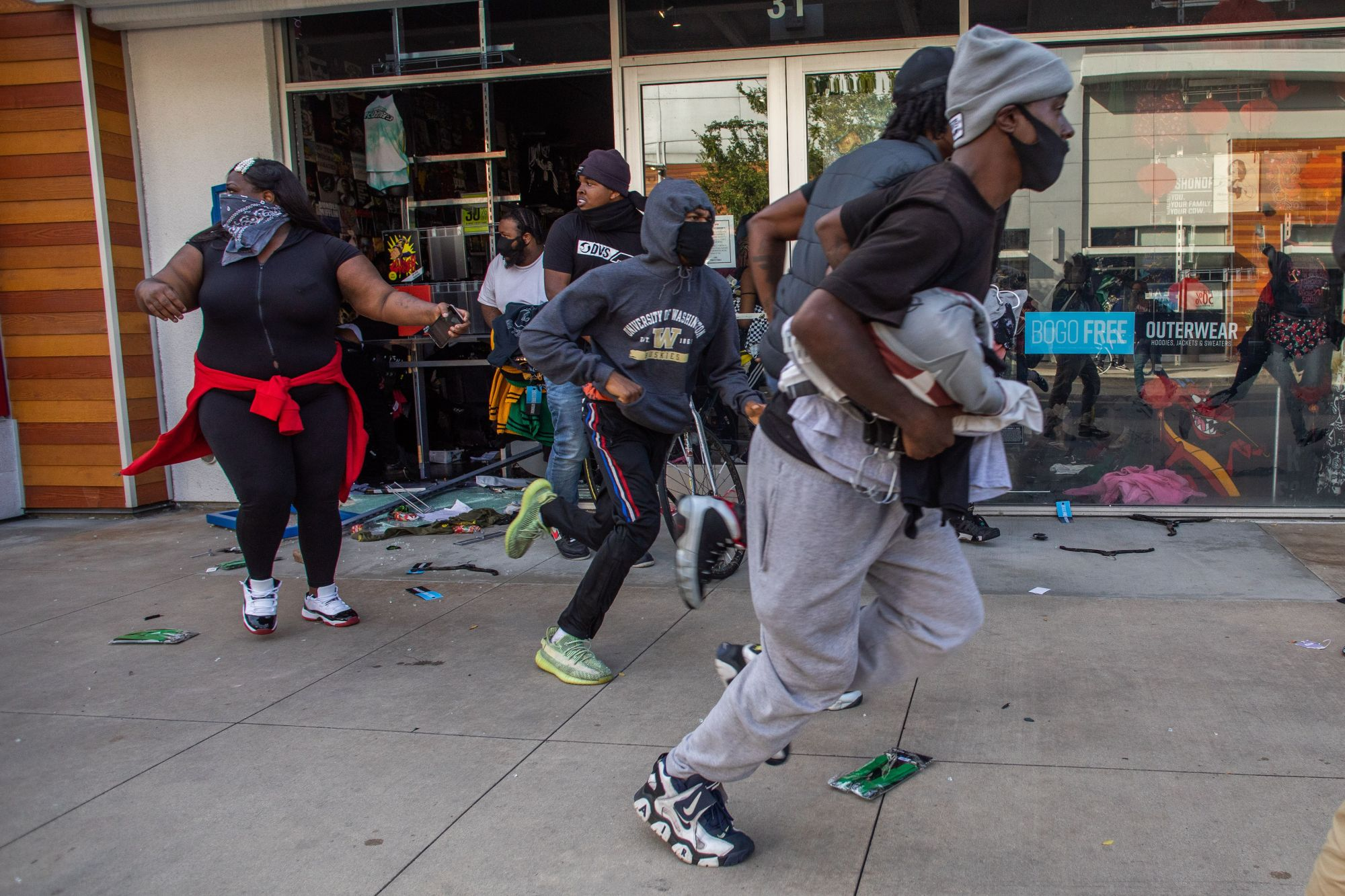 People run with items looted in a clothing store in downtown Long Beach on May 31, 2020 during a protest against the death of George Floyd. (APU GOMES/AFP via Getty Images)