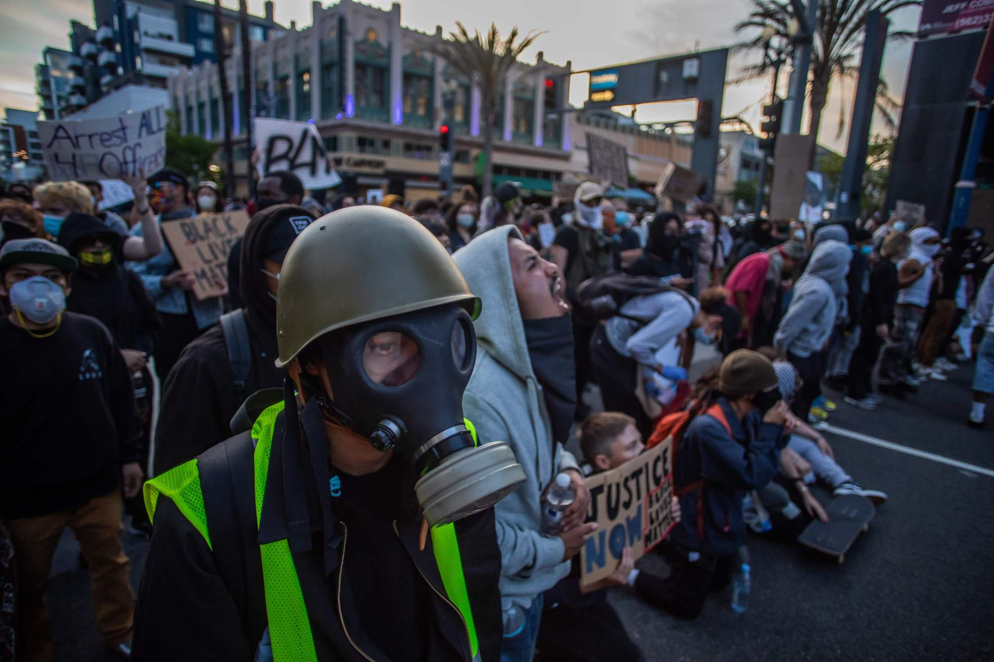 A man wearing a gas mask stands in front of a Police line in Downtown Long Beach on May 31, 2020, during a protest against the death of George Floyd. (APU GOMES/AFP via Getty Images)