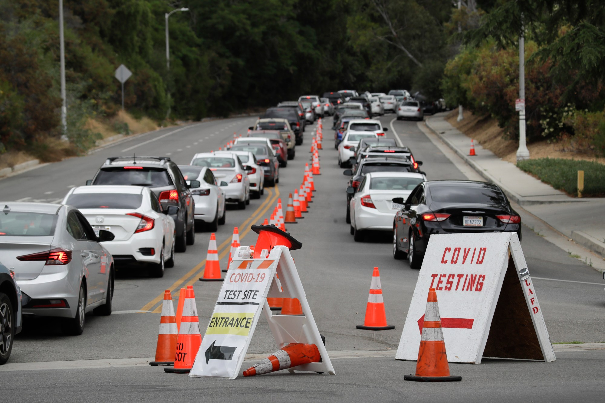 Motorists line up at a coronavirus testing site at Dodger Stadium Monday, June 29, 2020, in Los Angeles. (AP Photo/Marcio Jose Sanchez)
